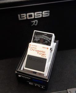 white Boss TU3 chromatic tuner pedal in front of Boss black amplifier