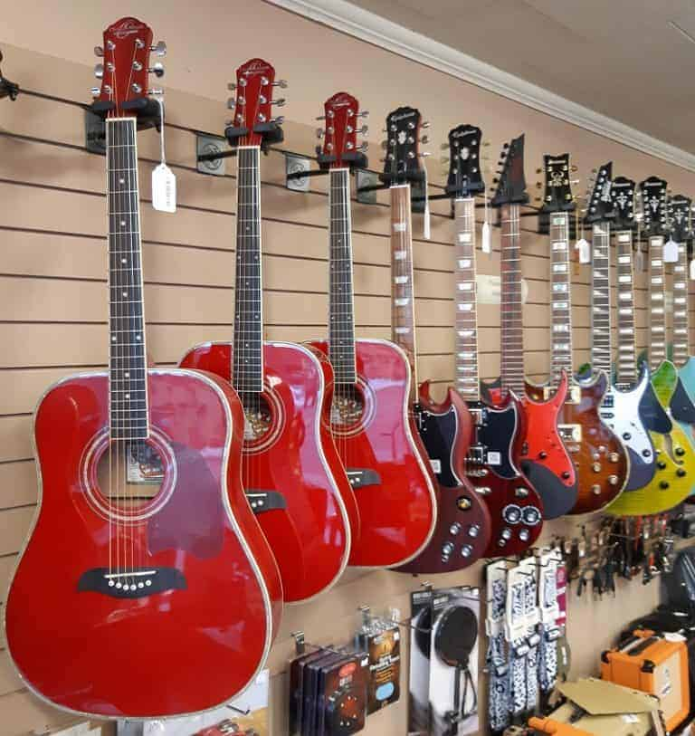 red acoustic and electric guitars hanging on wall