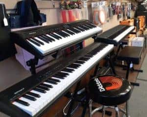 3 black Roland keyboards on stands
