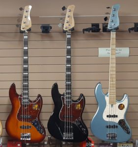 Sire basses hanging on a wall in sunburst, black and metalic blue
