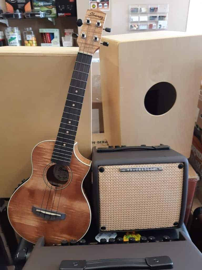 Wood grain Ibanez ukulele leaning on acoustic amp